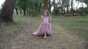 Немногое красивая девушка в красивом розовом платье с улыбкой на ее стороне идя в природу, замедленное движение видеоматериал