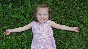 Немногое милая девушка в платье лежит на лужайке и усмехаться видеоматериал