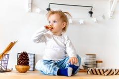 Немногое милая девушка малыша есть печенье овса и сидя на кухонном столе стоковые изображения rf