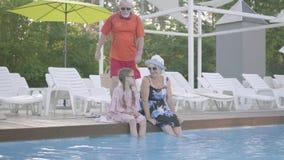 Немногое милая девушка с отрезками провода и зрелой женщиной сидя на краю бассейна с их ногами в воде видеоматериал