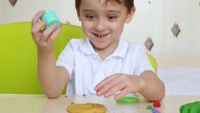 Немногое милый мальчик сидит на таблице и играх с пластилином Счастливые, смешные прессформы ребенка от модельного смешивания для сток-видео