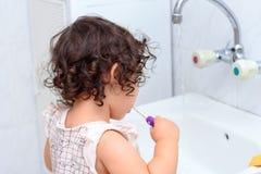 Немногое милый ребенок очищая ее зубы с зубной щеткой в bathroom стоковое фото