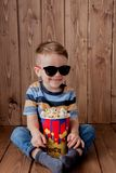 Немногое милый ребенок ребенк 2-3 лет старого, стекла кино 3d держа ведро для попкорна, есть фаст-фуд на деревянной предпосылке м стоковая фотография rf