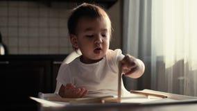 Немногое милый ребенок сидя на таблице и играя с карандашами акции видеоматериалы