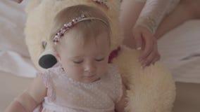 Немногое ребенок в розовом платье лежа на игрушке медведя дома пока руки ее матери чистя ее волосы щеткой с видеоматериал