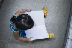 Немногое ребенок исследует и читающ книгу во взгляде сверху книжного магазина стоковое фото