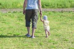 Немногое ребенок ребенка 1 - летний идет держать руку папы Отец идет с ребенком через зеленую траву Младенец учит t стоковое изображение rf