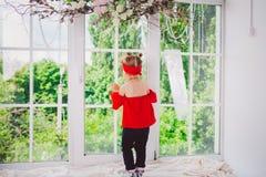 Немногое смешные 2 года старого ребёнка в стильных красных стойках одежд и джинсов и тапок с задней частью на windowsill около вы стоковое изображение