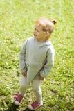 Немногое счастливая рыжеволосая девушка бежит на зеленой траве и нагревает в солнце лета в парке детей стоковое изображение rf