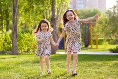 Немногое счастливые девушки на прогулке на вечере лета на заходе солнца в парке Сестры стоковая фотография