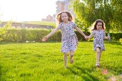 Немногое счастливые девушки на прогулке на вечере лета на заходе солнца в парке Сестры стоковая фотография rf