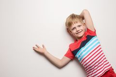 Немногое усмехаясь мальчик в футболке изолированной на белой предпосылке r стоковое изображение rf