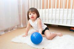Немного 2 года мальчика играют с шариком фитнеса внутри помещения Стоковые Фотографии RF