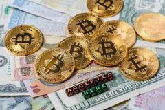 Немного золотых монеток с знаком bitcoin и ` надписи признавали здесь ` на предпосылке бумажных денег различного countr Стоковая Фотография
