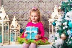 Немного довольно курчавая белокурая усмехаясь девушка сидя на рождественской елке windowsill почти Стоковое Изображение