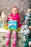 Немного довольно курчавая белокурая усмехаясь девушка сидя на рождественской елке windowsill почти Стоковая Фотография