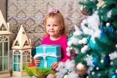 Немного довольно курчавая белокурая усмехаясь девушка сидя на рождественской елке windowsill почти Стоковые Изображения RF