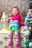 Немного довольно курчавая белокурая усмехаясь девушка сидя на рождественской елке windowsill почти Стоковая Фотография RF