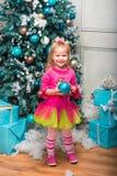 Немного довольно курчавая белокурая усмехаясь девушка стоя почти рождественская елка Стоковое Фото