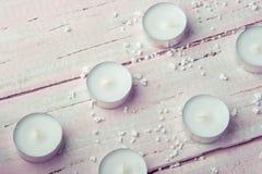 Немного плоских белых свечей на красивом деревянном столе Стоковые Фото