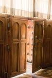Немножко раскрытая деревянная дверь с занавесами шнурка над ей Стоковое Фото