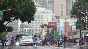 ненастная погода Ребеята школьного возраста с шестерней дождя спешат через занятую улицу города видеоматериал