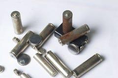 Ненужные батареи разных видов разбросаны На белой предпосылке Стоковая Фотография RF