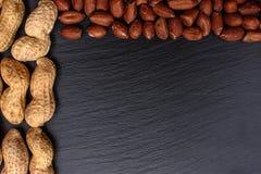 Необработанные арахисы и слезанный на черной каменной доске, космосе для текста Стоковое Фото