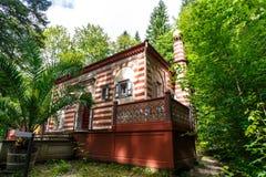 Необыкновенный красный и белый striped дом с патио Стоковые Изображения RF