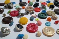 Необычно разнообразная серия яркого пестротканого разнообразия круглых кнопок, различных текстур, диаметра, на белой предпосылке Стоковые Фотографии RF