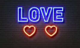 Неоновая вывеска влюбленности на предпосылке кирпичной стены стоковая фотография