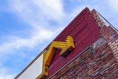 Неоновая вывеска желтой стрелки в кирпичном здании стоковые фотографии rf