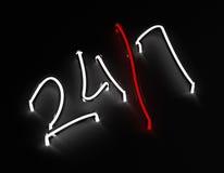 24 / неоновая вывеска 7 на черной предпосылке Стоковое фото RF