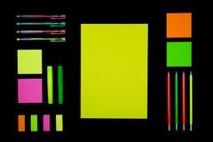 Неоновые бумага и канцелярские принадлежности на черноте стоковые изображения rf
