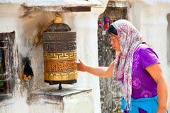 Неопознанная женщина делать молить катит внутри Катманду, Непал. Стоковые Фотографии RF