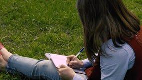 Неопознанная женщина пишет в тетради видеоматериал