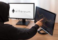 Неопознанная персона которое указывает экран ethereum Стоковая Фотография RF