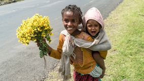 Неопознанная эфиопская девушка при брат младенца продавая цветки на обочине Стоковые Изображения