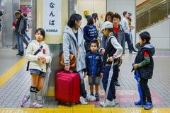 Неопознанное японское familky ожидание для поезда на станции Namba Стоковое Фото