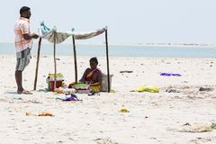 Неопознанные арахисы плодоовощей надувательства женщины к клиенту, под шатром на пляже Danushkodi стоковое изображение rf