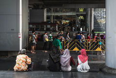 Неопознанные девушки сидя на шаге, и неопознанные люди ждать шину на Сиаме центризуют Стоковые Фото