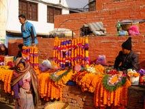 Неопознанные женщины делают цветки поклонению в квадрате Bhaktapur Durbar, Катманду, Непале Стоковые Изображения