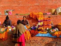 Неопознанные женщины делают цветки поклонению в квадрате Bhaktapur Durbar, Катманду, Непале Стоковое Изображение
