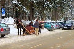 Неопознанные люди на тележке лошади в снежном городке Zakopane стоковые фотографии rf