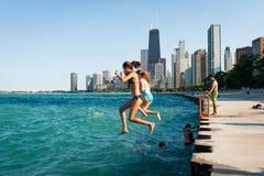 Неопознанные подростки скачут в Lake Michigan в Чикаго, IL Стоковое Изображение RF