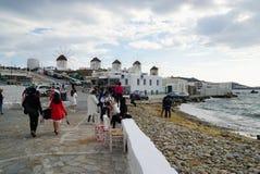 Неопознанные туристы посещают ветрянки на острове Mykonos, Греции Стоковая Фотография