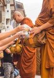 Неопознанные туристы предлагая липкий рис к буддийскому монаху внутри стоковые фотографии rf