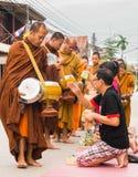 Неопознанные туристы предлагая липкий рис к буддийскому монаху внутри стоковое фото