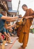 Неопознанные туристы предлагая липкий рис к буддийскому монаху внутри стоковая фотография