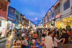 Неопознанные туристы ходят по магазинам на старом рынке ночи городка вызваны Шпиком Yai в Пхукете, Таиланде Стоковые Изображения RF